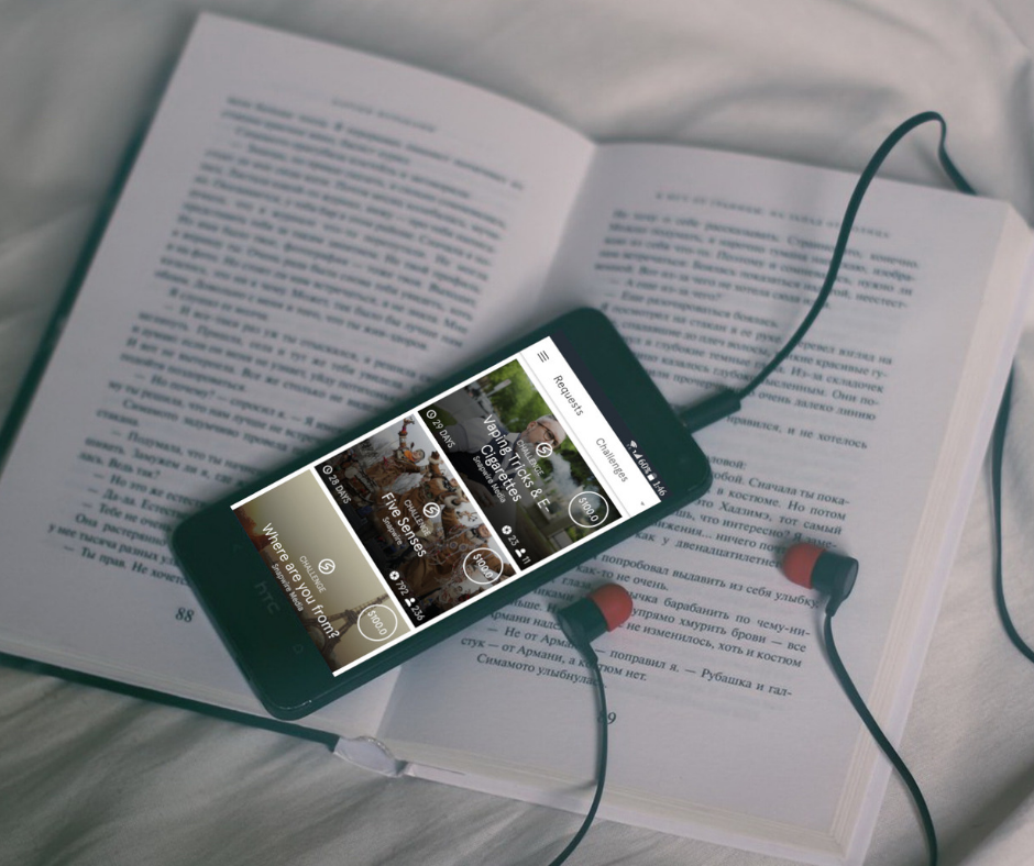 A screenshot of the Snapwire app on a smartphone connected to headphones, lying on a book on a bed.