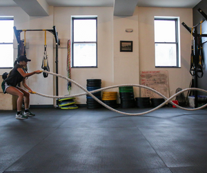 A lady doing battle ropes in the gym.
