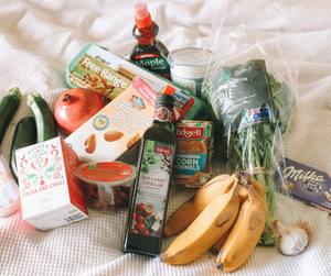 Grocery products scattered over the bed after a visit to the grocery store.