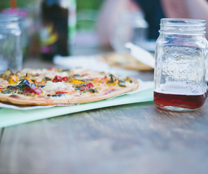A pizza besides a mason jar containing juice on a table at a restaurant.