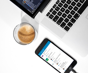 A cup of tea besides a laptop and a smartphone that displays job opportunities available on the LinkedIn app.