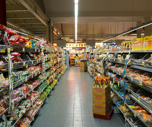 The snacks lane in a supermarket that has plenty of snacks on each side.