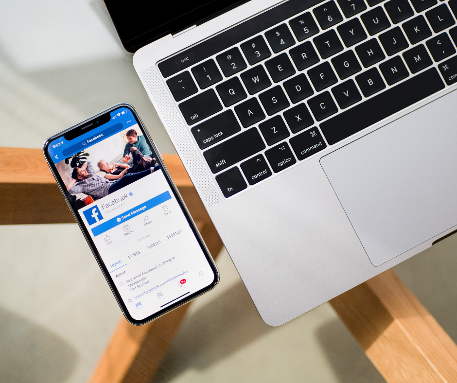 Facebook app opened to apply for jobs on a smartphone beside a laptop on a desk.