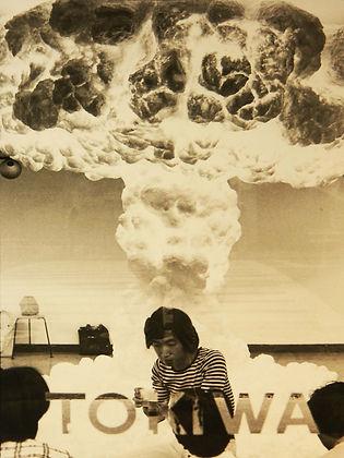 日本橋の画廊に展示されたキノコ雲の前にたたずむたべ・けんぞう