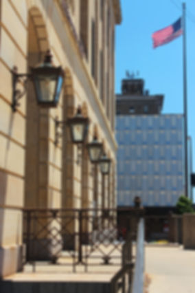 View of historic lamps on library building on a sunny day walking up the ramp with American flag flying in the breeze
