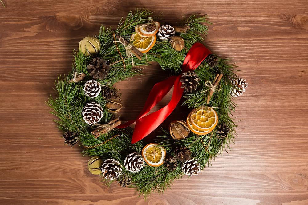 атмосферу праздника! Его вешают на стены и окна, а в виде горизонтальной композиции он является украшением праздничного стола. Рождественский венок над порогом – это ваш семейный оберег, символ надежды на счастье, благополучие и достаток, а также приглашение для гостей. Мы использовали только натуральные компоненты при создании венка: сосновые ветки, шишки, апельсин, корица.