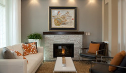 beige-elongated-sofas-and-fireplace-on-burnt-orange-living-room-with-natural-sto