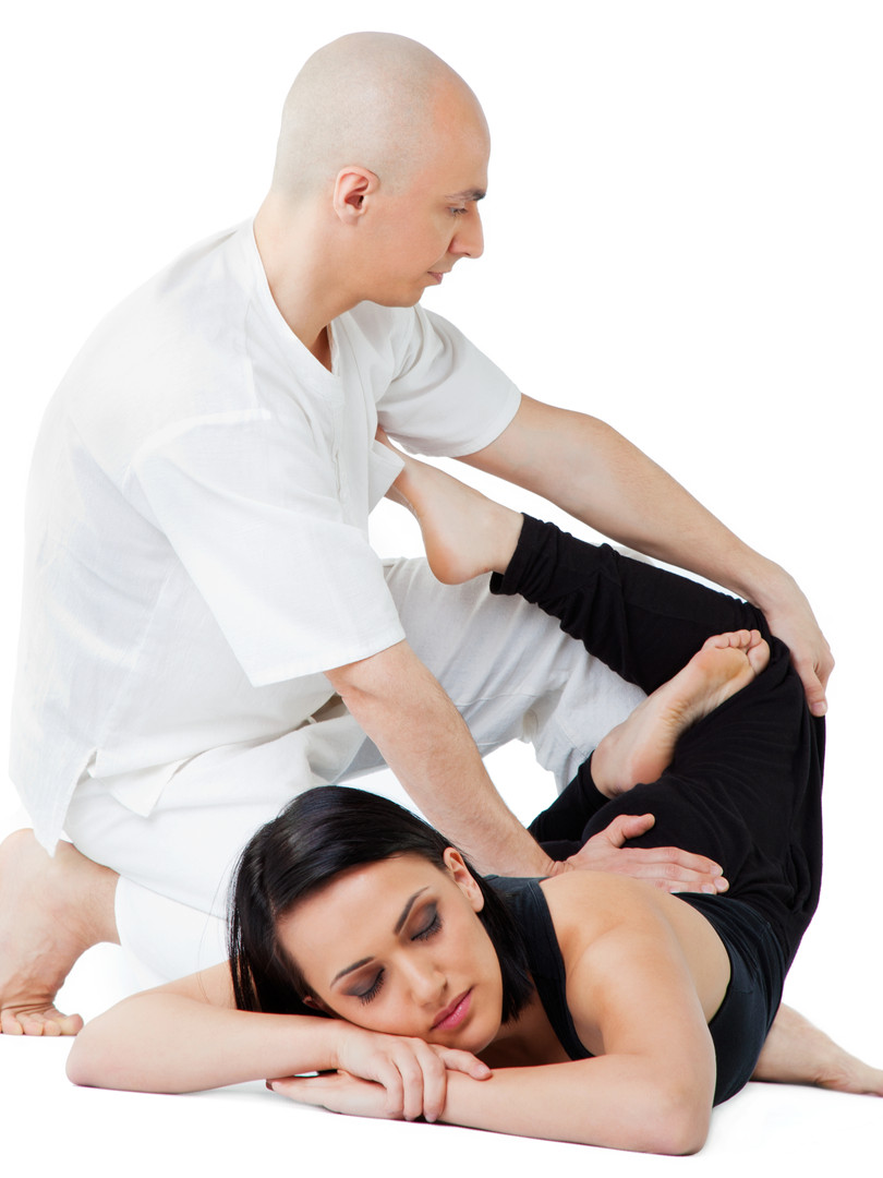 Young female receiving massage in thai position by therapist, eyes closed