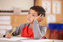 Portrait of a boy daydreaming in an elem