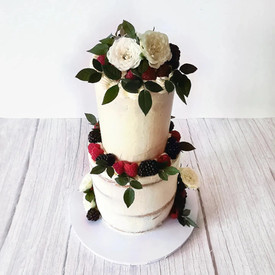 Semi naked, two-tier wedding cake with white roses and fresh berries