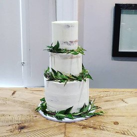 Three-tier, semi naked wedding cake with eucalyptus garlands