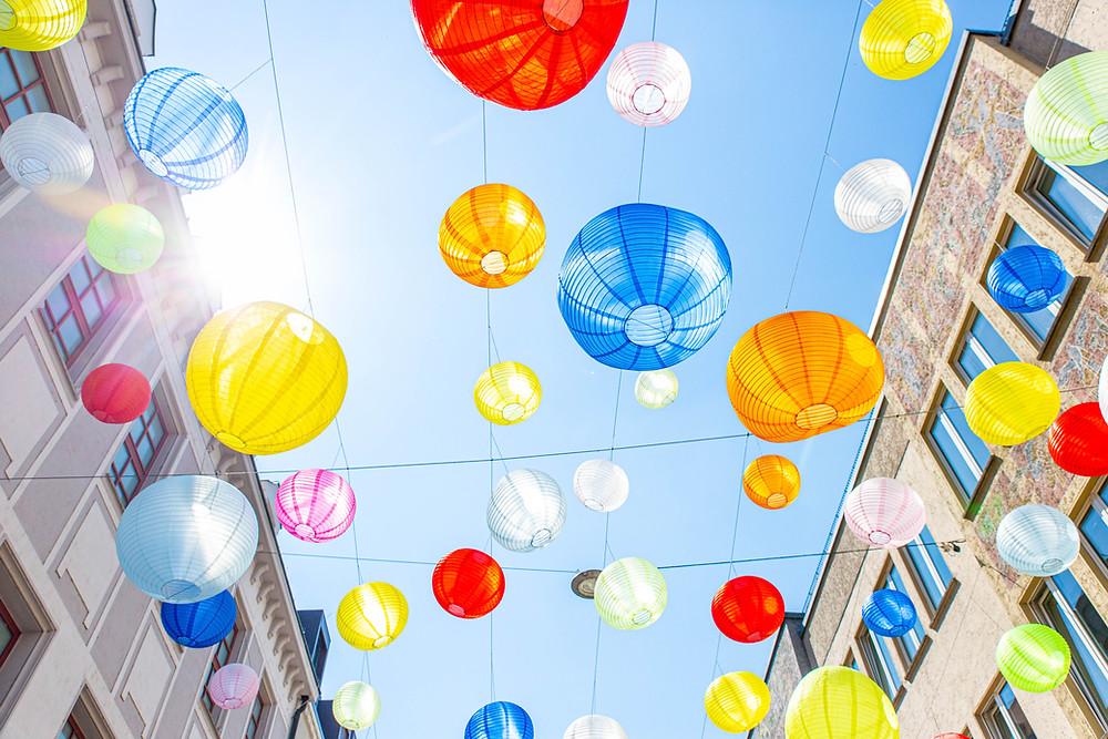 Das Foto zeigt bunte Lampions. Sie strahlen mit der Sonne um die Wette.