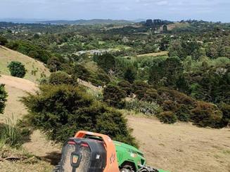 Mowing long grass on steep farm land
