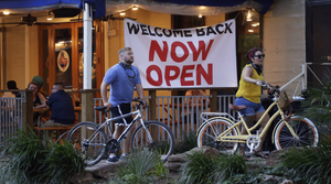 Visitors to the River Walk pass a restaurant that reopened in San Antonio last last month. Like other states, Texas continues to reopen despite the persistence of the COVID-19 pandemic.