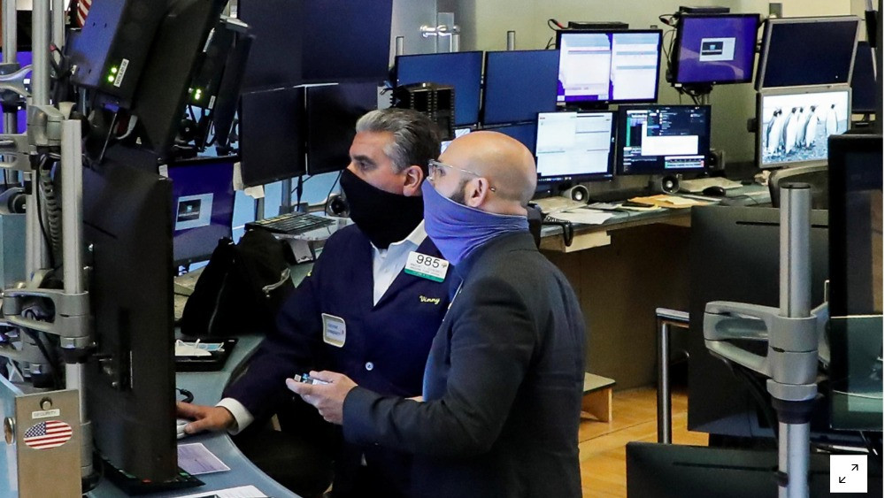 FILE PHOTO: Traders wearing masks work, on the first day of in person trading since the closure during the outbreak of the coronavirus disease (COVID-19) on the floor at the New York Stock Exchange (NYSE) in New York, U.S., May 26, 2020. REUTERS/Brendan McDermid