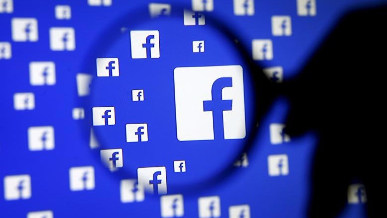 A man poses with a magnifier in front of a Facebook logo on display in this illustration taken in Sarajevo, Bosnia and Herzegovina, December 16, 2015. REUTERS/Dado Ruvic/File Phot