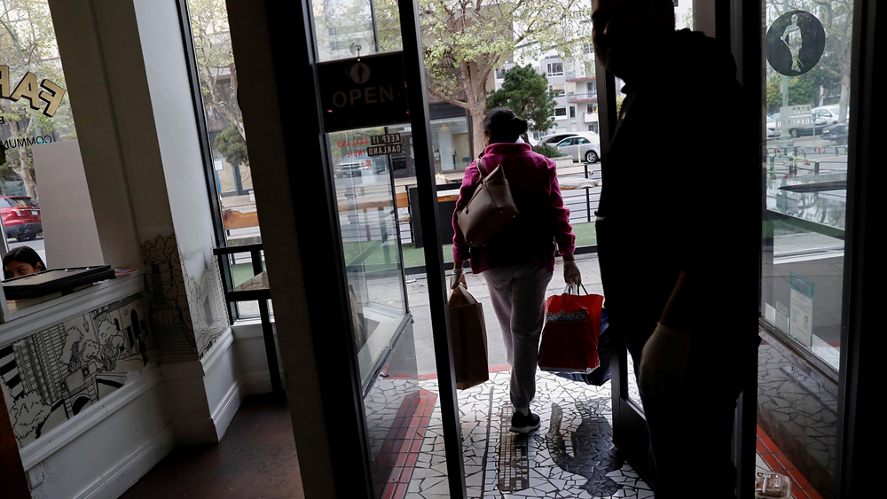 An employee of Farley's East cafe, that closed due to the financial crisis caused by the coronavirus disease (COVID-19), carries donated food items after being laid off from the cafe in Oakland, California, U.S. March 18, 2020. REUTERS/Shannon Stapleton/File Photo
