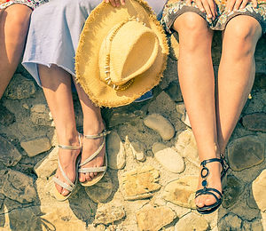Four girlfriends sitting on a wall outdoors with spring and summer dresswear - Women meeting and hav