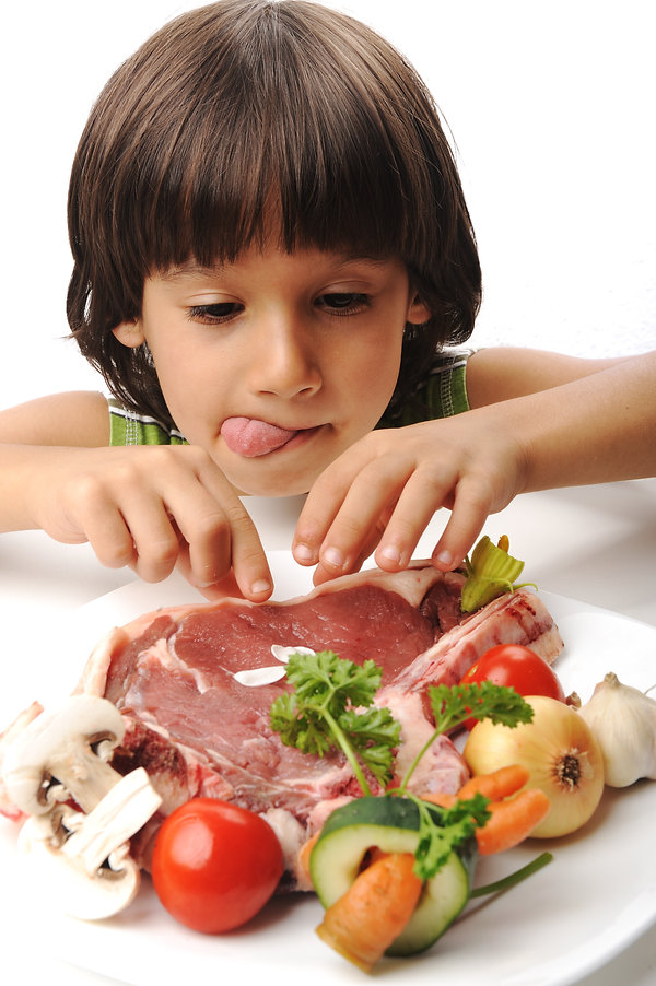 Cute positive boy and raw meat and veget