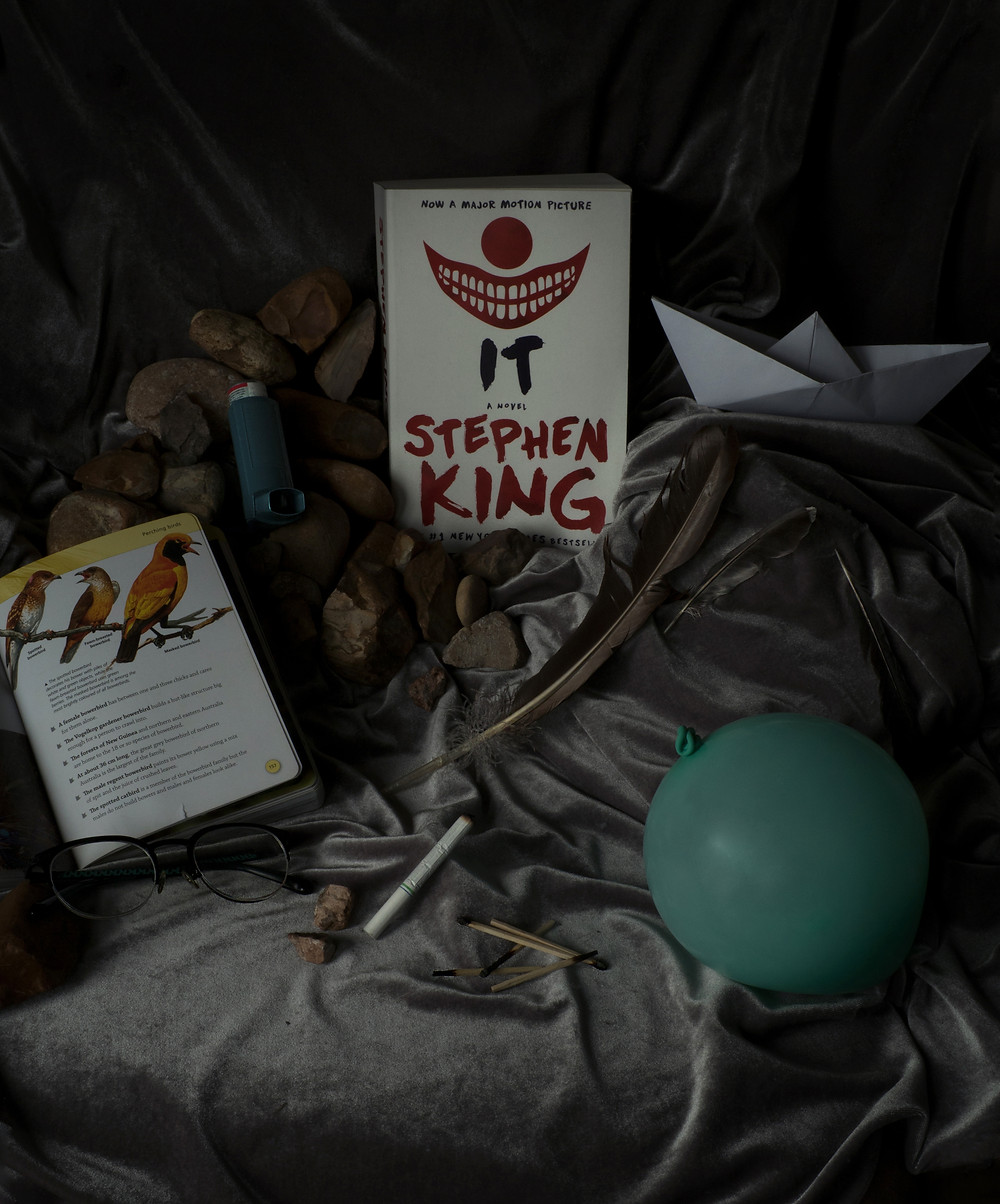 A paper back copy of Steven King's It standing as the focal point surrounded by items pertaining to the story. Circling around from top right to bottom right: a paper boat, a large pile of rocks, an inhaler, an encyclopedia of birds, glasses, a large feather with two smaller feathers on the side, a cigarette, matches, and a balloon