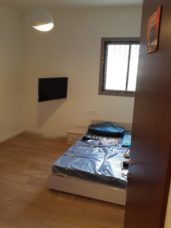 תליית טלויזיה על הקיר לחדר שינה