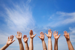 volunteering concept, hands of group of people volunteers in blue sky