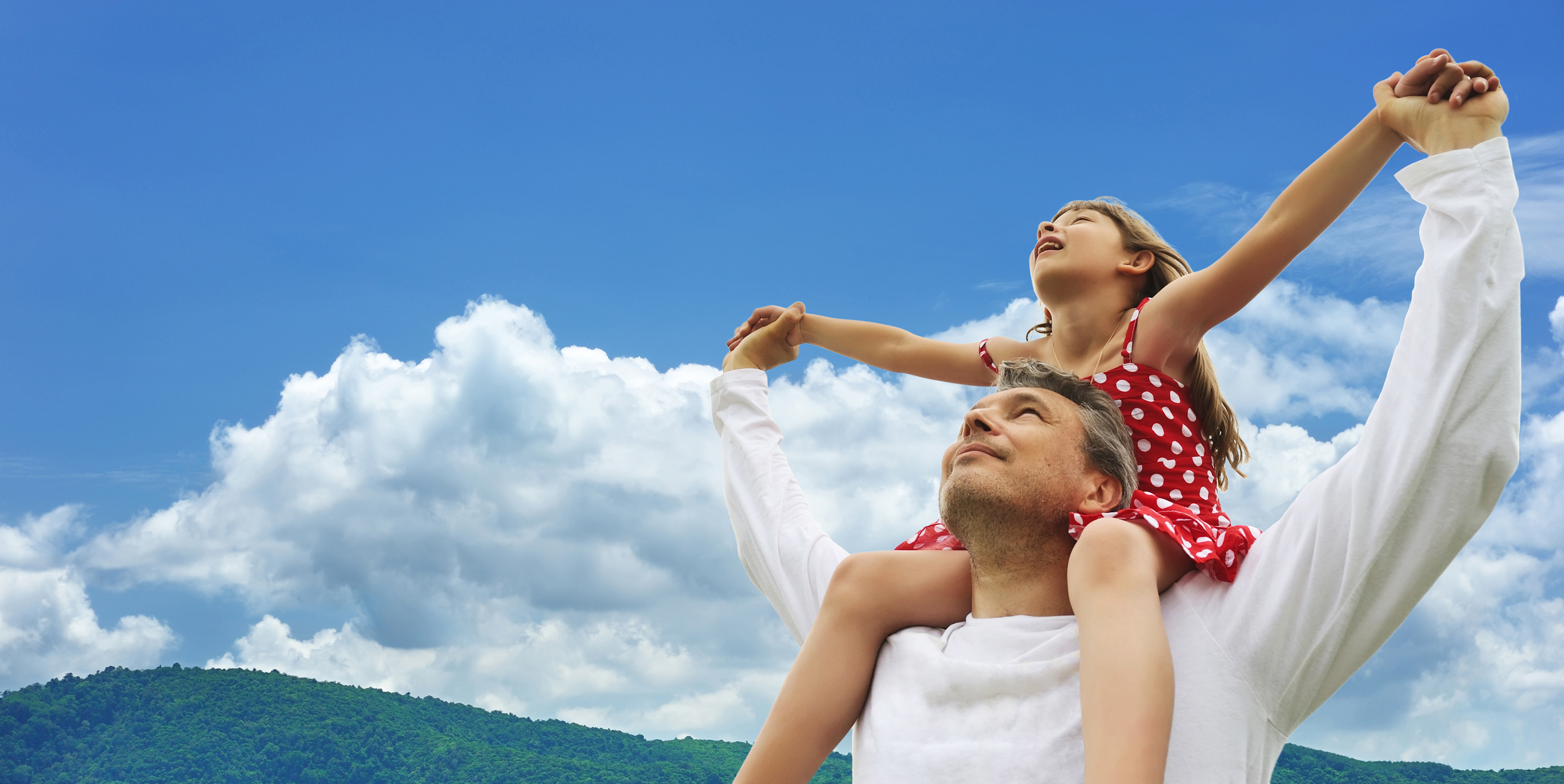 Father and daughter on shoulders against sky