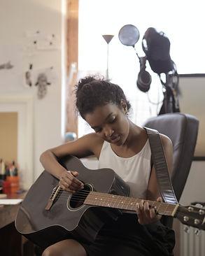 woman-in-white-tank-top-playing-guitar-3