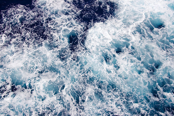 Image of disturbed ocean, waves crashing on rocks.