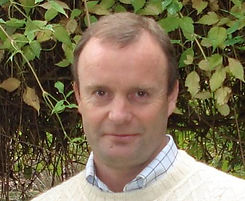 David Toohey, middle aged gentlemen wearing collared shirt with sweater over it.