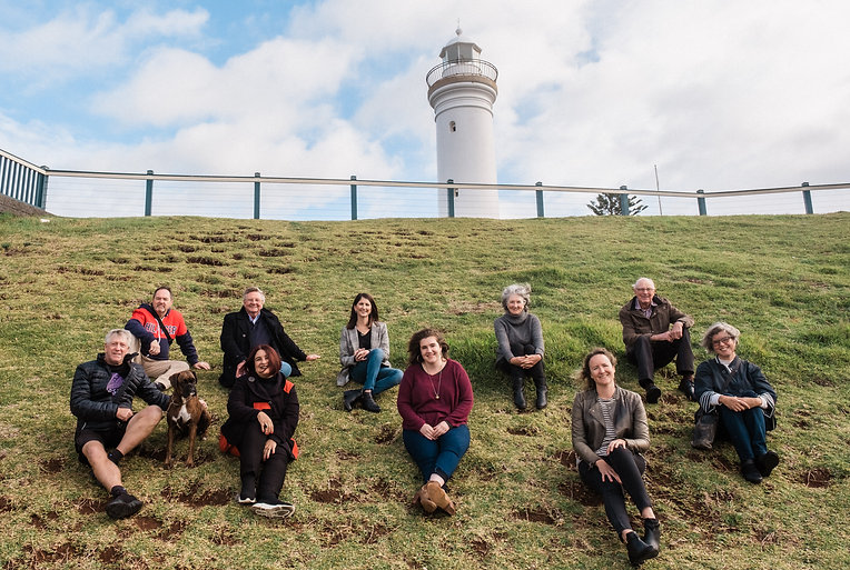 Image or founding volunteers sitting on hill in front of the Kiama Lighthouse.