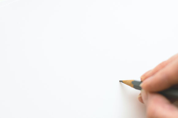 Close up of hand holding a pencil writing nothing on a white background.