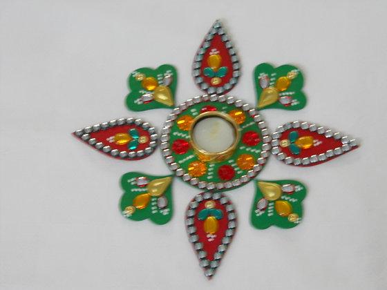 Red green rangoli with metal diya