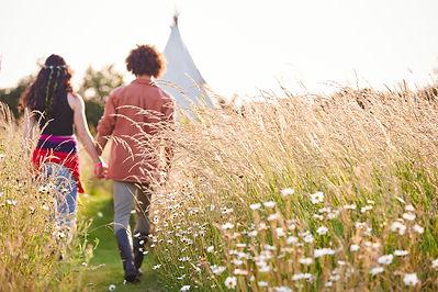 young-romantic-couple-walking-through-fi