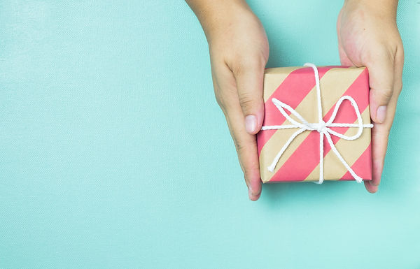 Hands holding craft paper gift box with