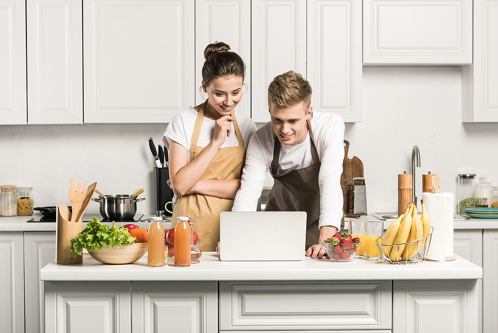 Adorable couple cooking at home with computer