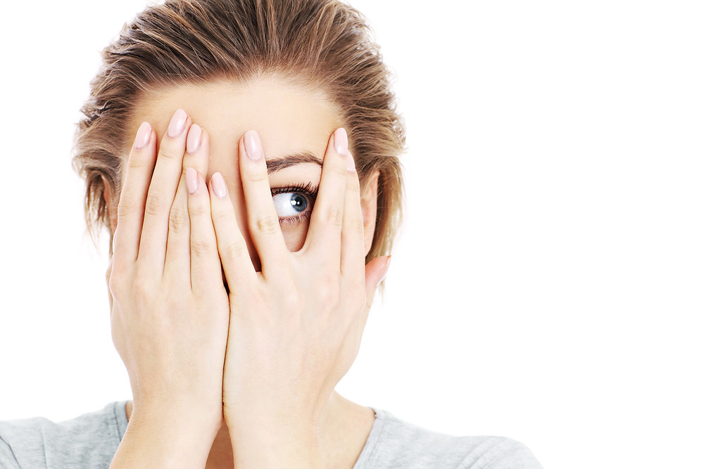 A picture of a scared woman covering her eyes over white background.jpg