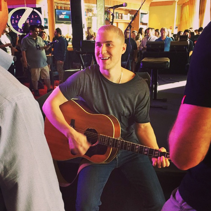 Alicia Love snaps a candid of Mike Posner before his performance.