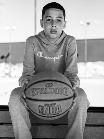 a-boy-seated-holding-a-basket-ball.jpg