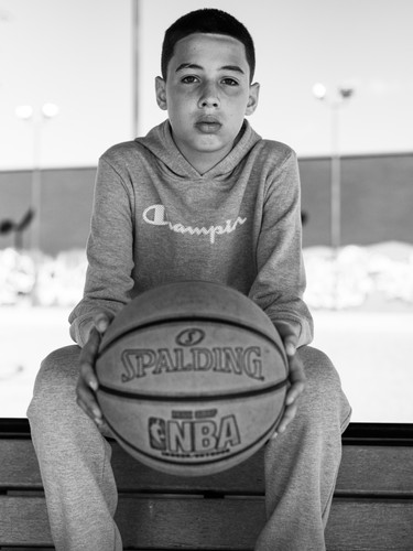 a-boy-seated-holding-a-basket-ball.jpg