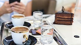 A person woman texing blogging with a tray of tukish coffe and cake