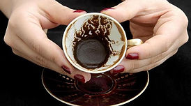 A woman holding a turkish coffee cup and reading a fortune teller