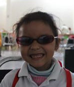 Girl with cheesy smile wears sunglasses