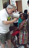 Volunteer uses handheld autorefractor on Jamaican girl