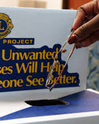 Spectacles being dropped in to a Lions Club donation box