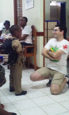 Vosh worker chats with Jamaican child with glasses