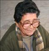 Elderly Woman uses two pairs of glasses to read
