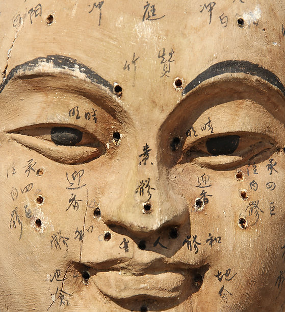 Ancient wooden face showing acupuncture