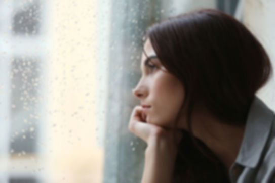 Depressed young woman near window at hom