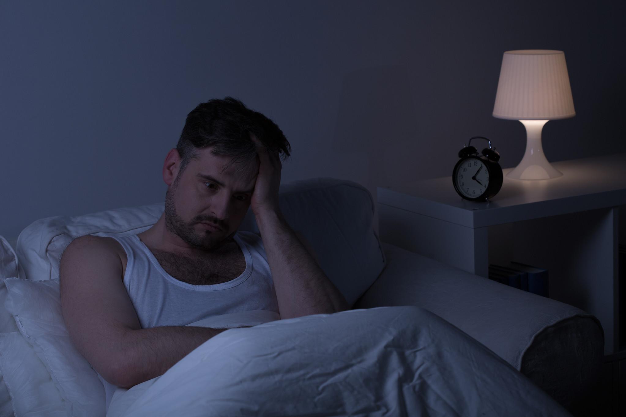 Man suffering from sleeplessness sitting